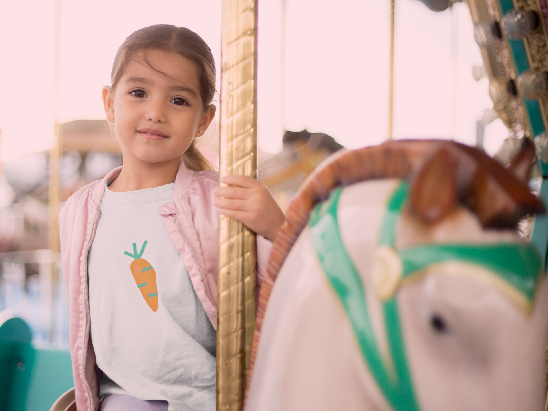 mockup-of-a-little-girl-riding-a-carousel-horse-wearing-a-tshirt-and-a-pink-jacket-22527.png