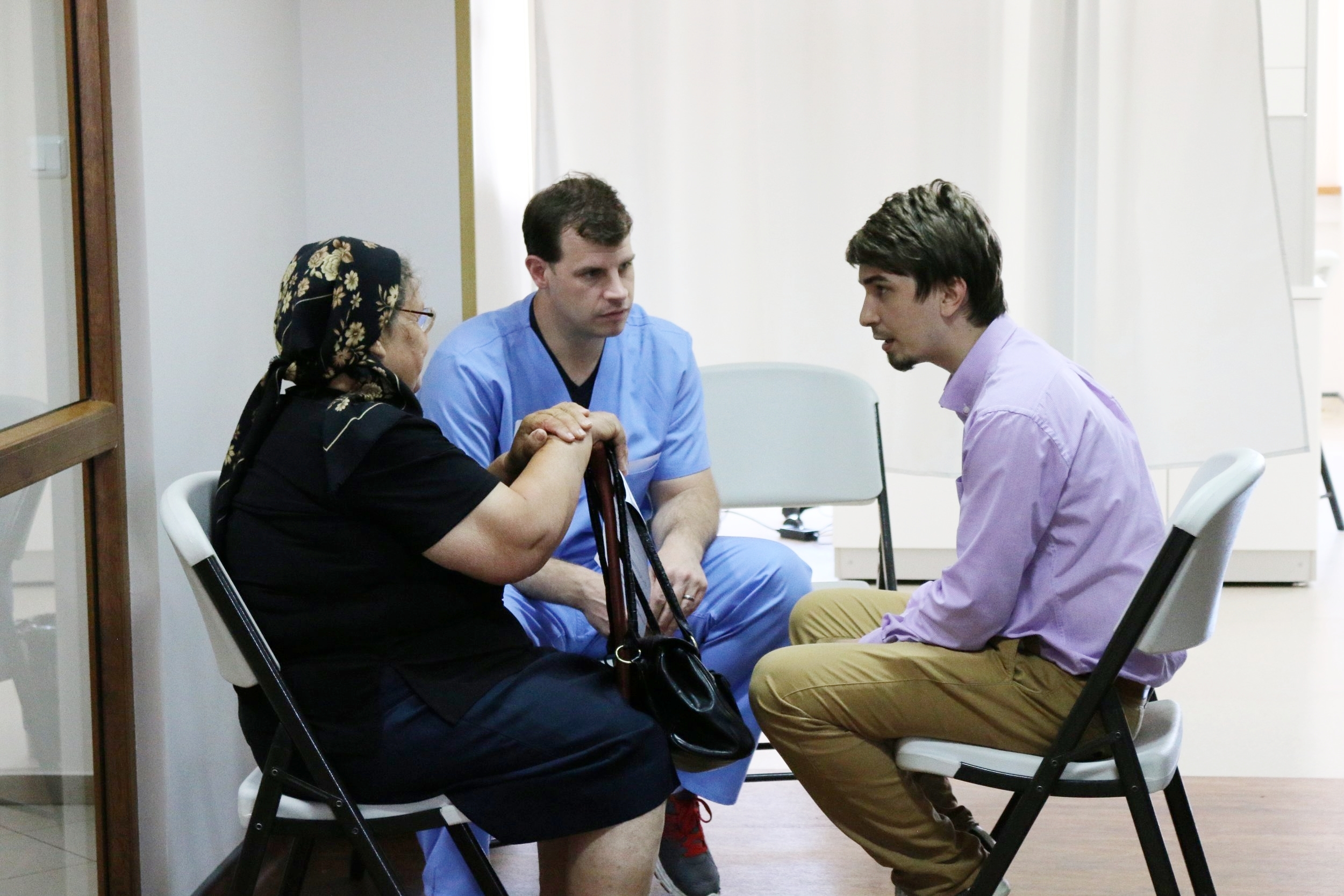 Lorne Book and Pastor Ioshua sharing the Gospel with Romanian patient in the Diaconia Medical Center waiting area.