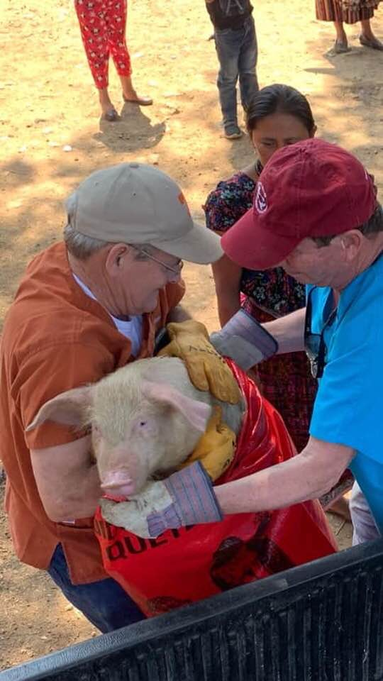 Scotty & John giving a pig to a family.jpg