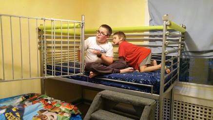 """Two growing brothers, one with a rare developmental disability & unable to walk, share a tiny room. Volunteers designed a bed with specialized steps for crawling and cool, """"big boy"""" railings."""