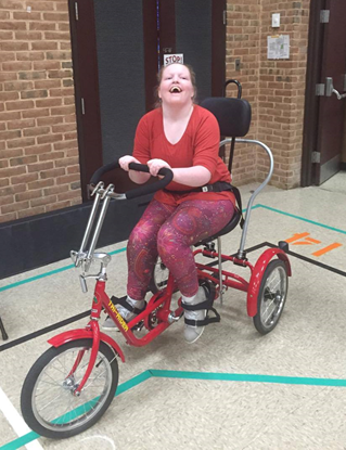 Isabelle is smiling, sitting in her modified bicycle.