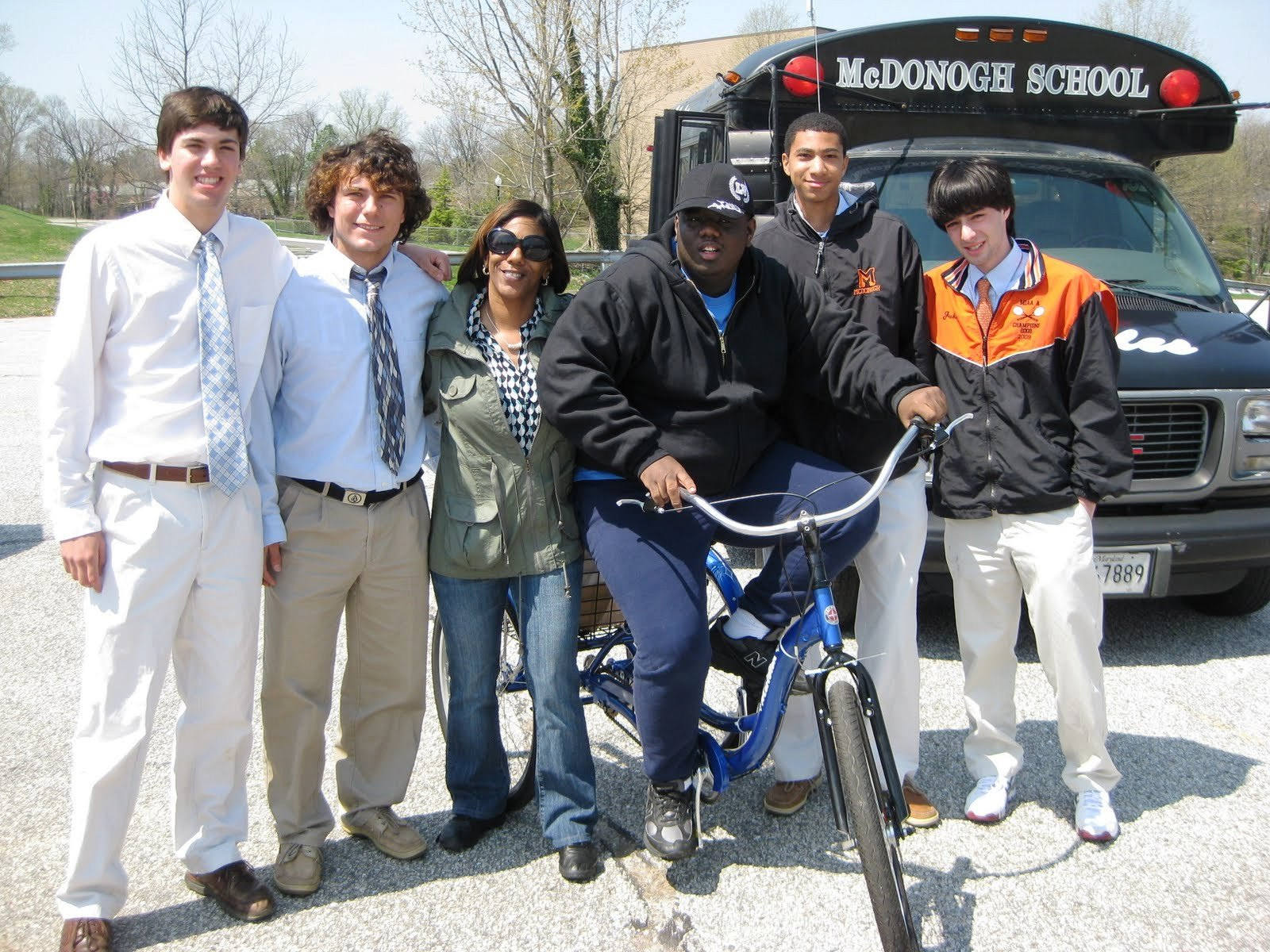 "Six people are standing outside, five gentlemen and one lady. One gentleman is sitting on a bicycle. A bus with the words ""McDonogh School"" is displayed."