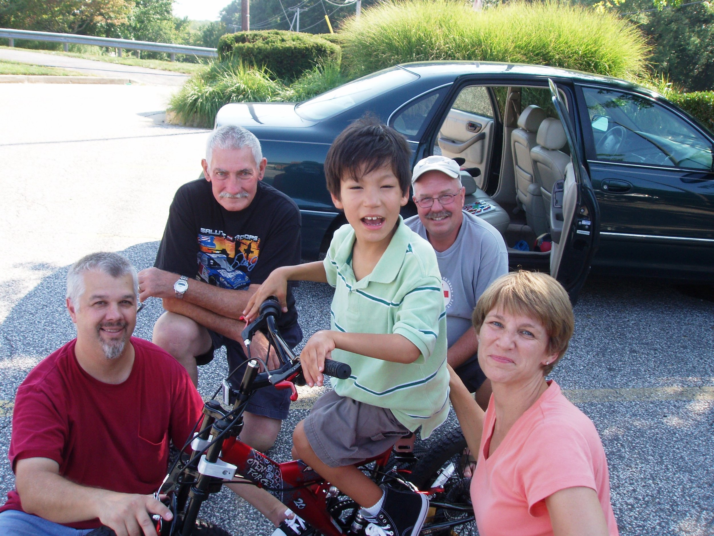 Five people are sitting outside, one is on a bicycle. A car with the back doors open is in the background.