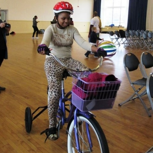 Young girl on bike indoors on a hardwood floor, smiling with items in a basket attached to the handlebars of the bicycle. Some chairs are in a row, ready for people to be seated. Other people doing various activities, a young person playing with a ball.