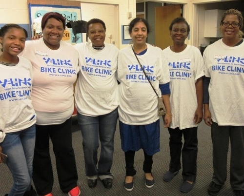 """Six people are standing indoors, all women, with a white t-shirt with the words """"V-Link Bike Clinic"""" in blue lettering."""