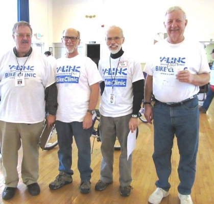 """Four gentlemen are standing indoors. They are wearing white t-shirts that says, """"V-Link Bike Clinic"""" in blue lettering."""