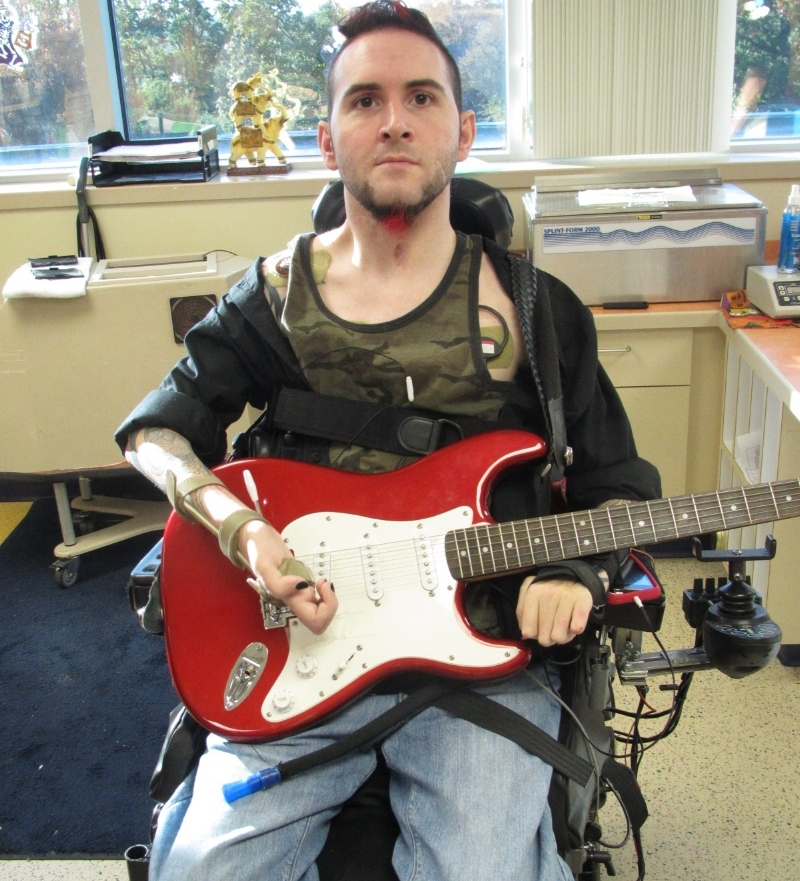 A gentleman sitting indoors in a chair holding a red and white guitar.