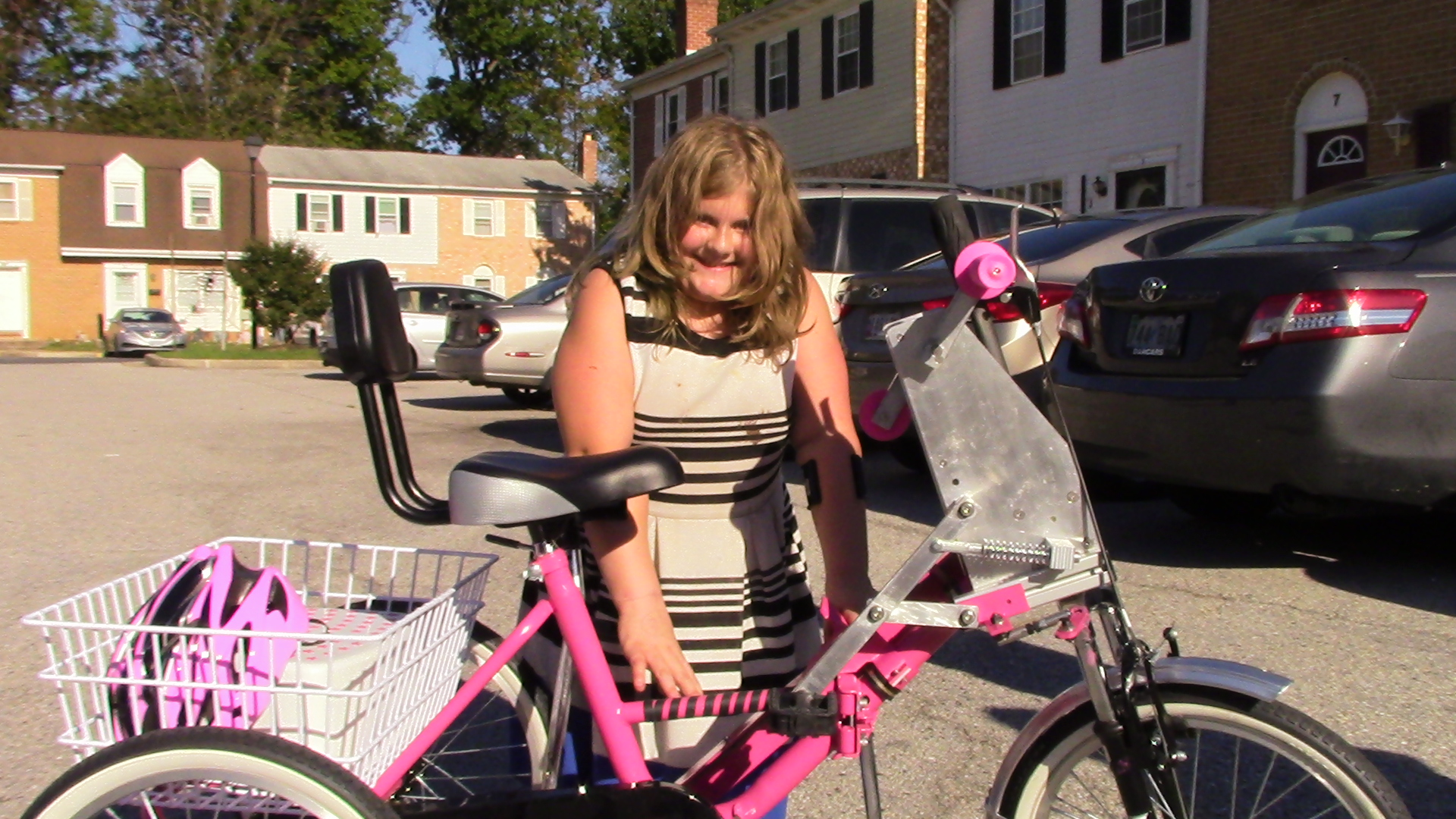 A young lady, outdoors, standing with a pink bicycle. Several cars are in the background in a parking lot.