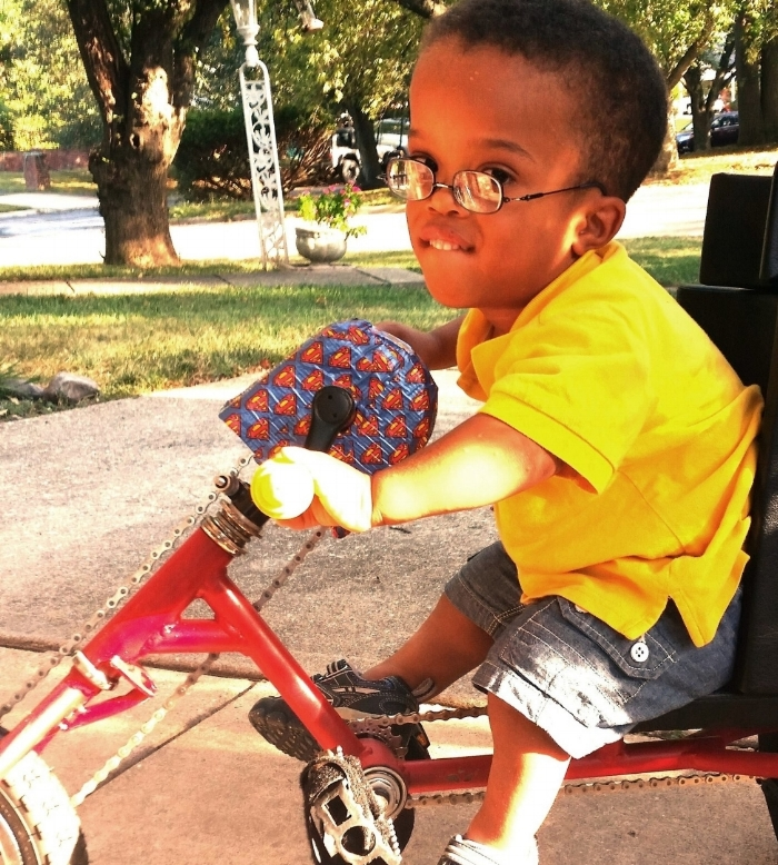 A young person riding a modified bicycle on a sidewalk.
