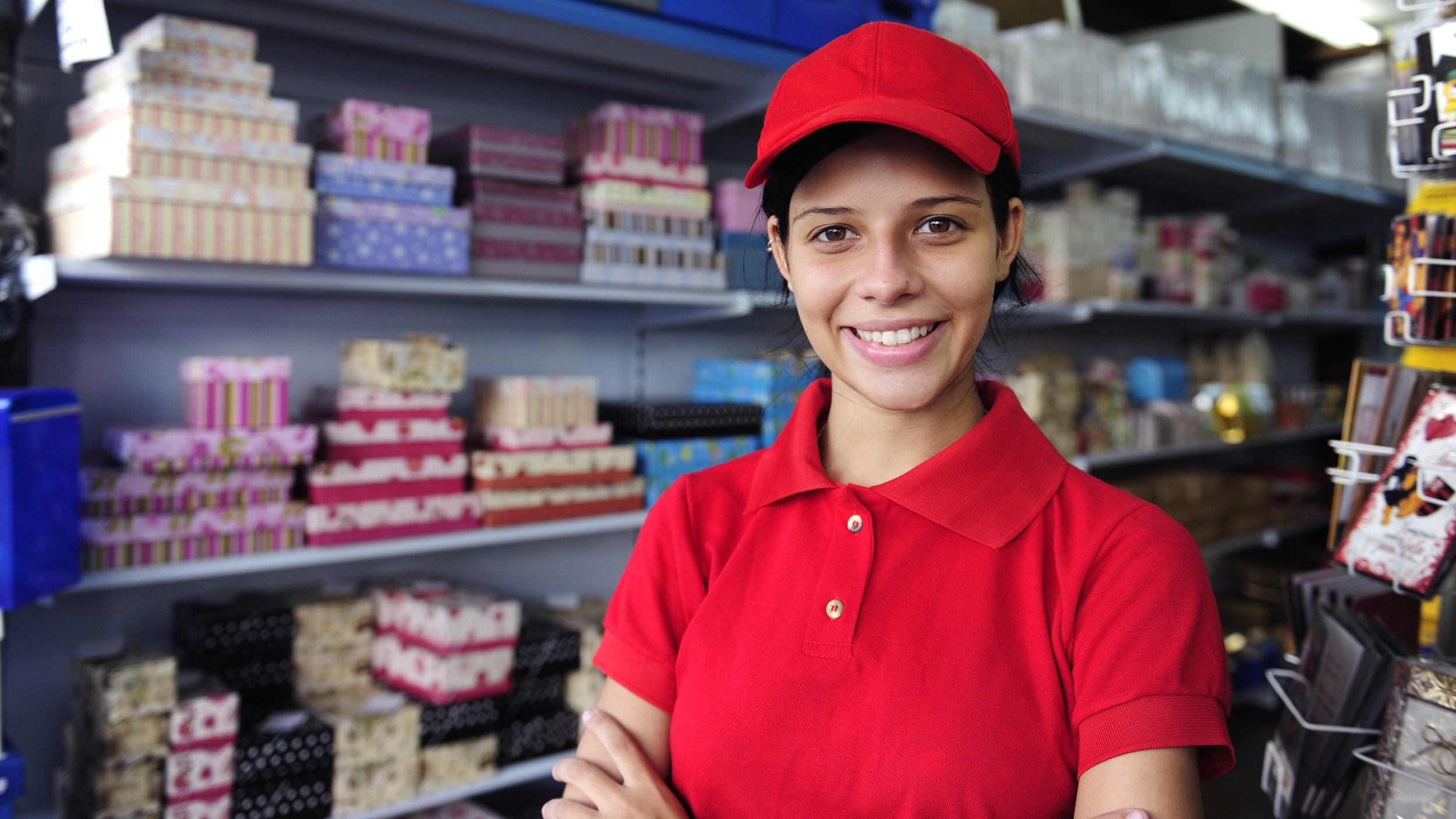 Woman wearing work uniform working in gift shop smiles