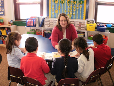 St. Adalbert students are working in a small group with their teacher on reading skills.