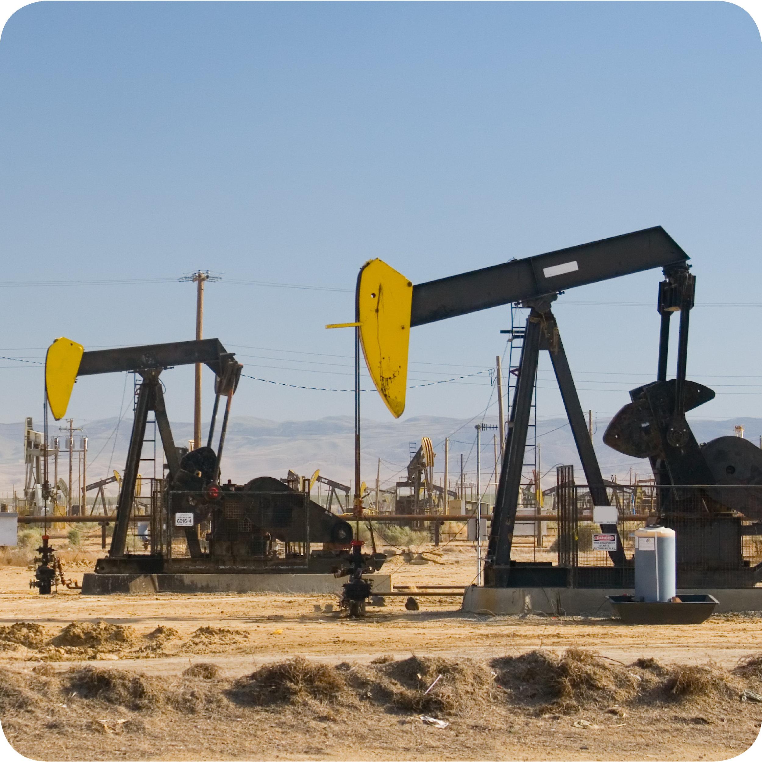 Two pumpjacks in an oil field.