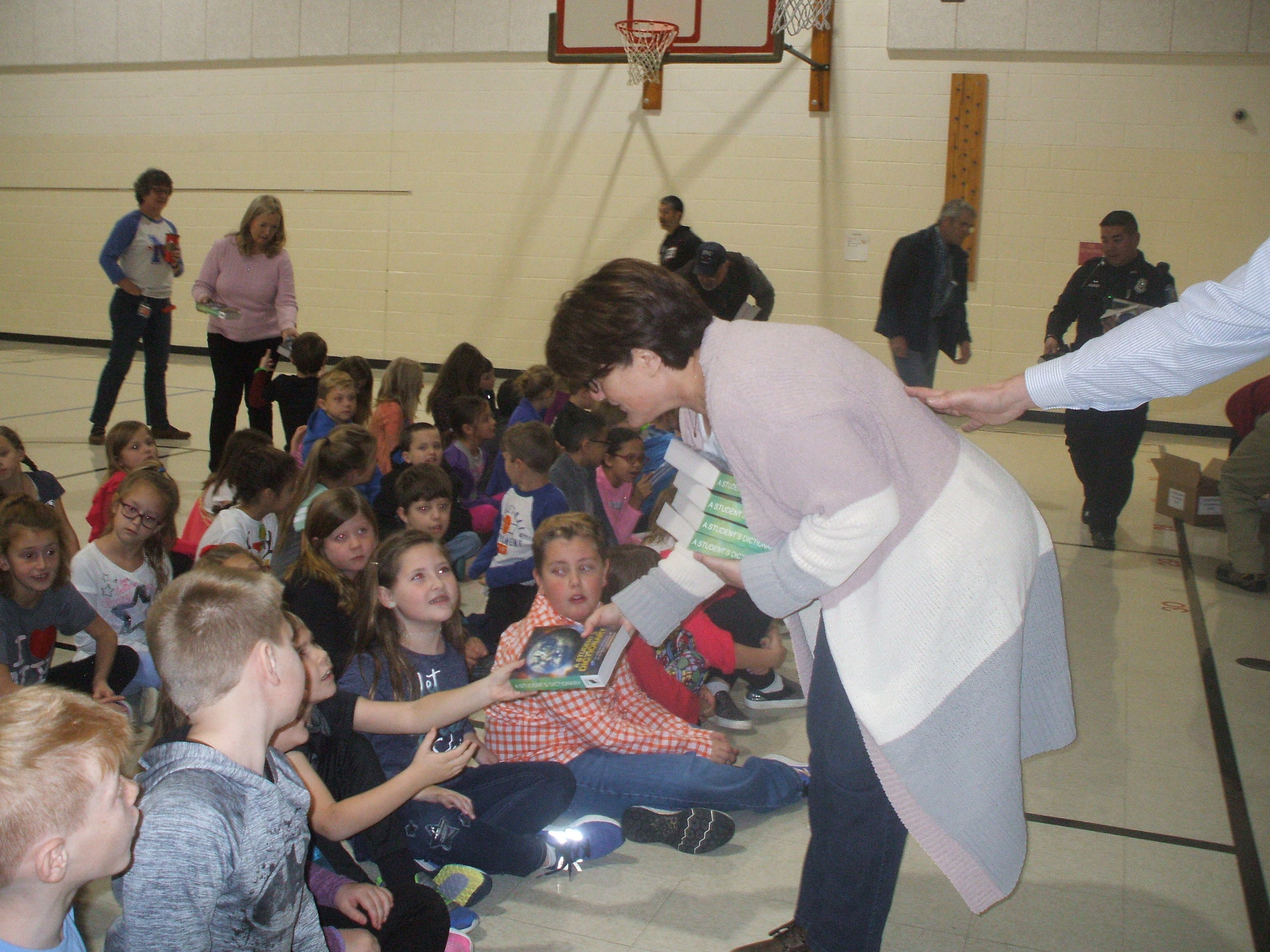 Member Betsy Spain is shown presenting a dictionary to her grandson at Edgewood Elementary School.