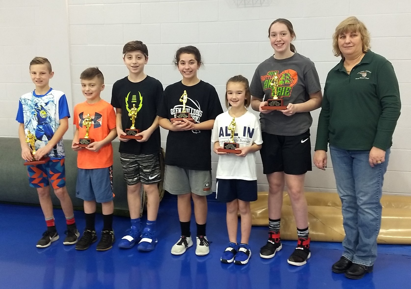 Left to right District Hoop Shoot  Winners: Ryan Turk (Lakewood), Chase Newsome (Ashtabula), Jaden Keenan (Kent), Ava Kouri (Kent), Paityn McCully (Alliance), Brooke Richmond ( Ashtabula) and Lisa Wadlow NE District Hoop Shoot Director.