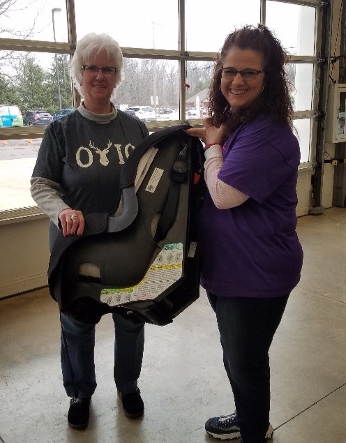 Debra Stall, PER and Suzanne Lewis from the Lodge attaches a sticker stating the car seat was donated from Ravenna Lodge #1076 and assists the Health Educator.
