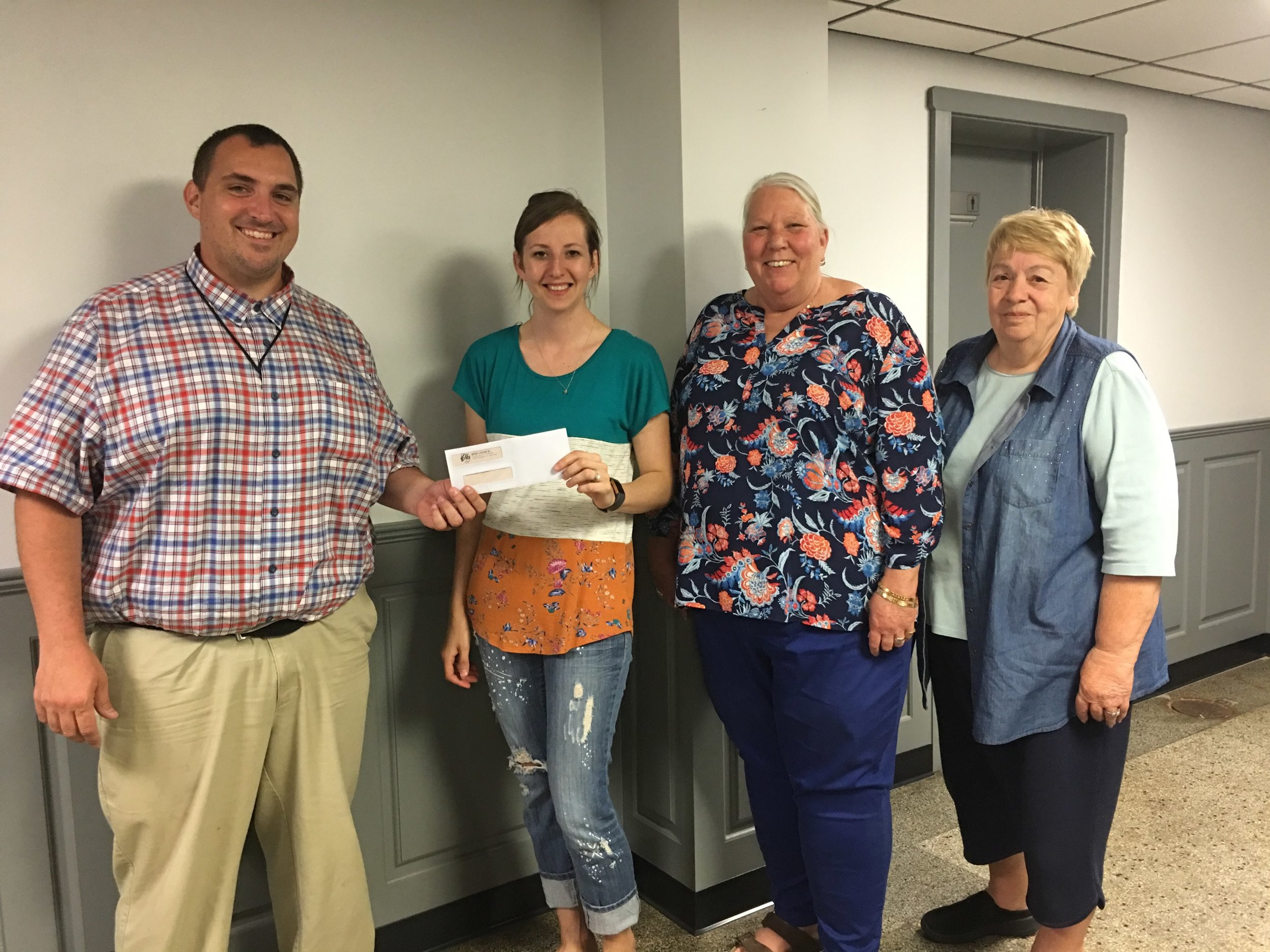 Presenting the check to Justin Swartz and Anne Denman are Elks members Megan Rowe and Donna Swavel.