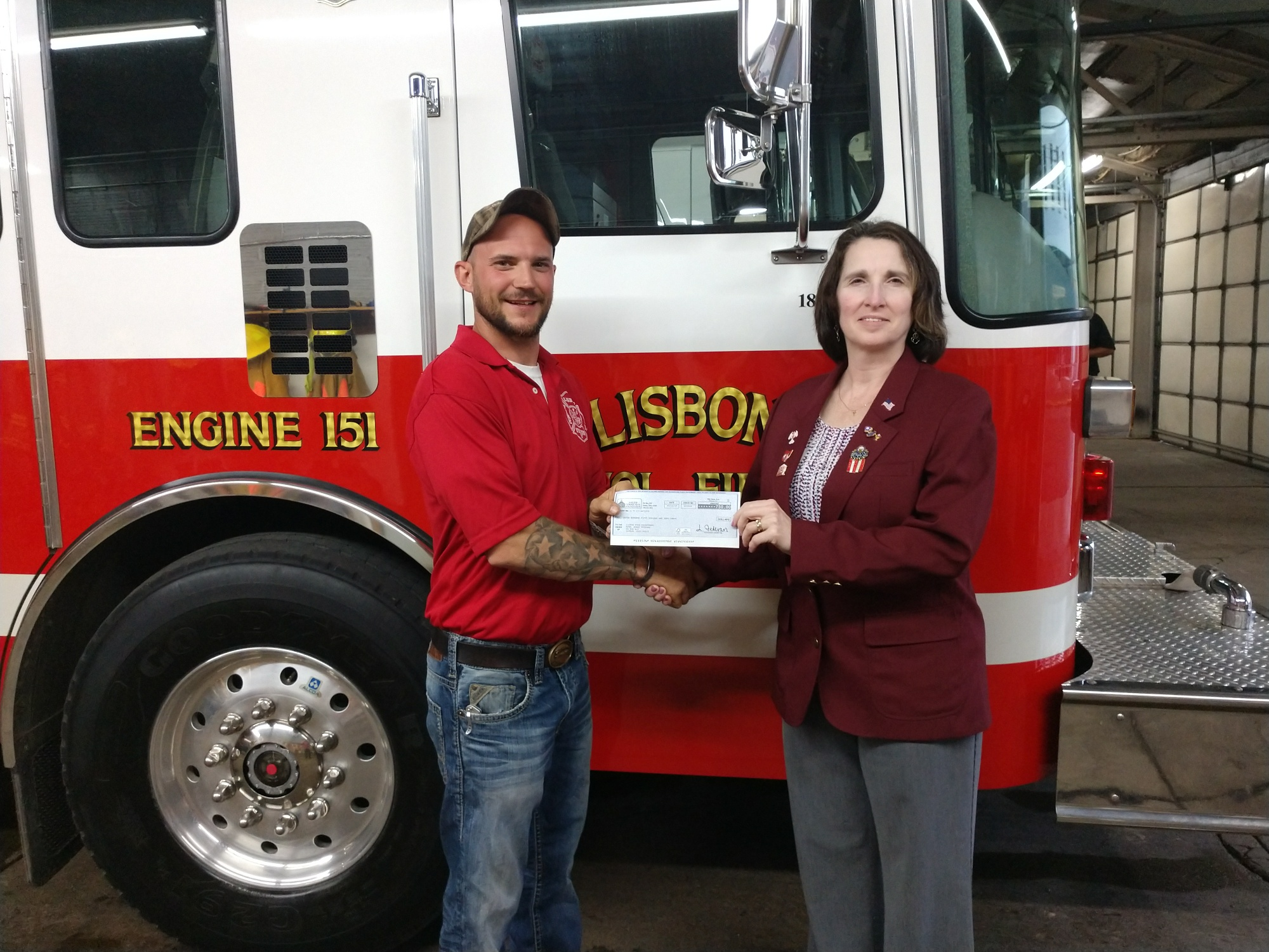 Presenting the check is Kim Chapman, Leading Knight to Bobby Huffman, Training Officer of the Lisbon FD.