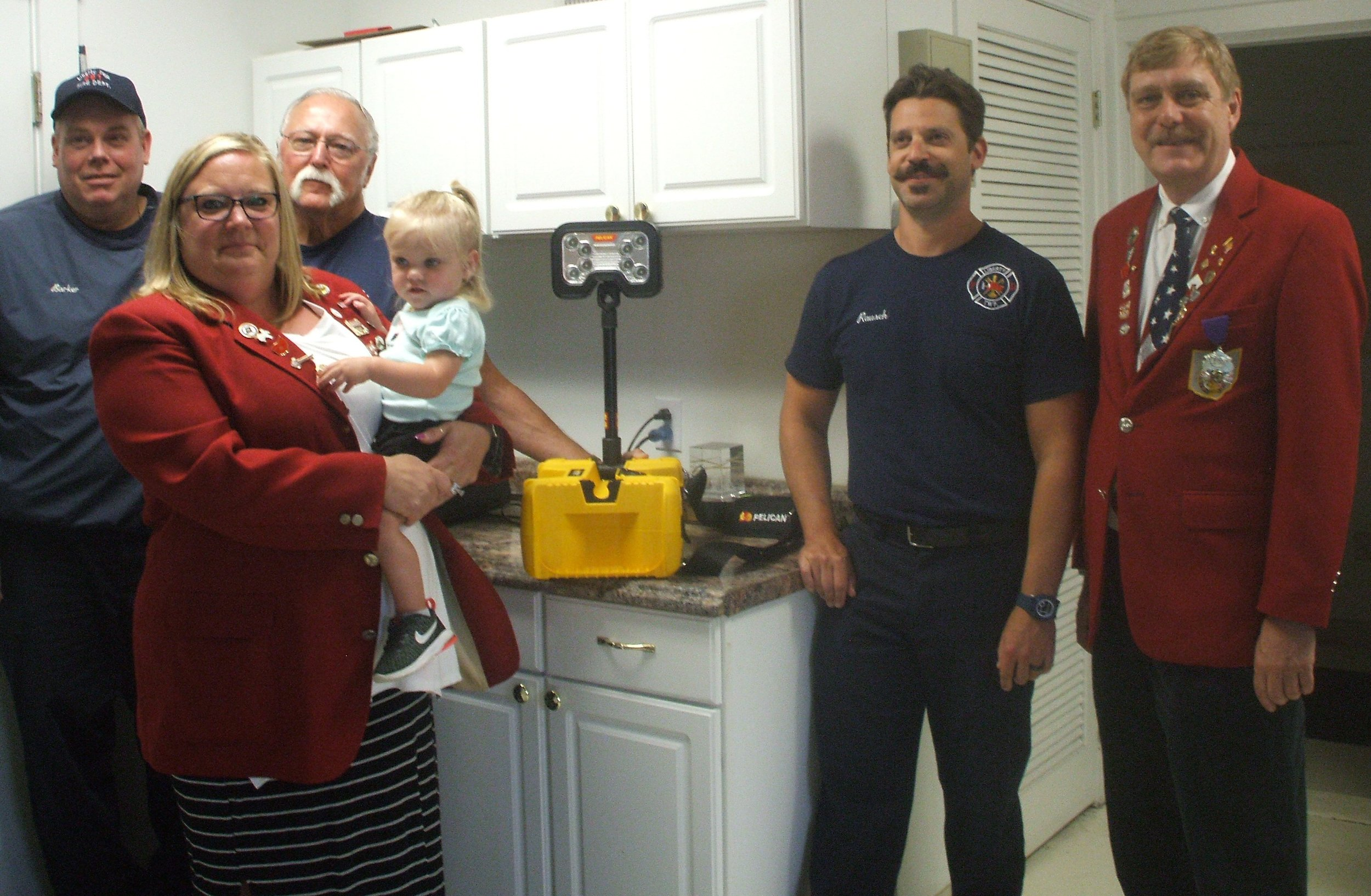 Shown presenting the Lighting system to the Fire Department are from left to right are:  Firefighter Dale Barker, Exalted Ruler Billie Jo Humble (holding Autumn), Liberty Township Fire Chief Lloyd Segner, Firefighter/Medic Jeremy Rausch, and Community Service Chairman Kermit Morse, III