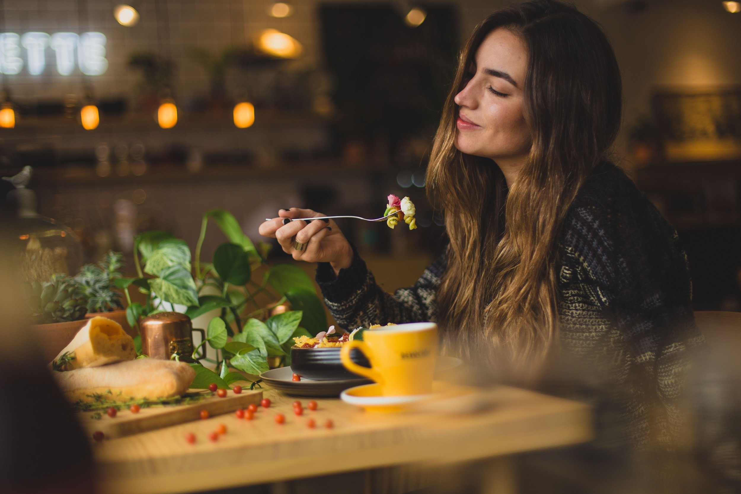 This lady looks like she is savoring the sights, smells, and taste of her food. Follow her example this holiday season by using all five senses when you eat. (  Pablo Merchán Montes    photo/   Unsplash  )