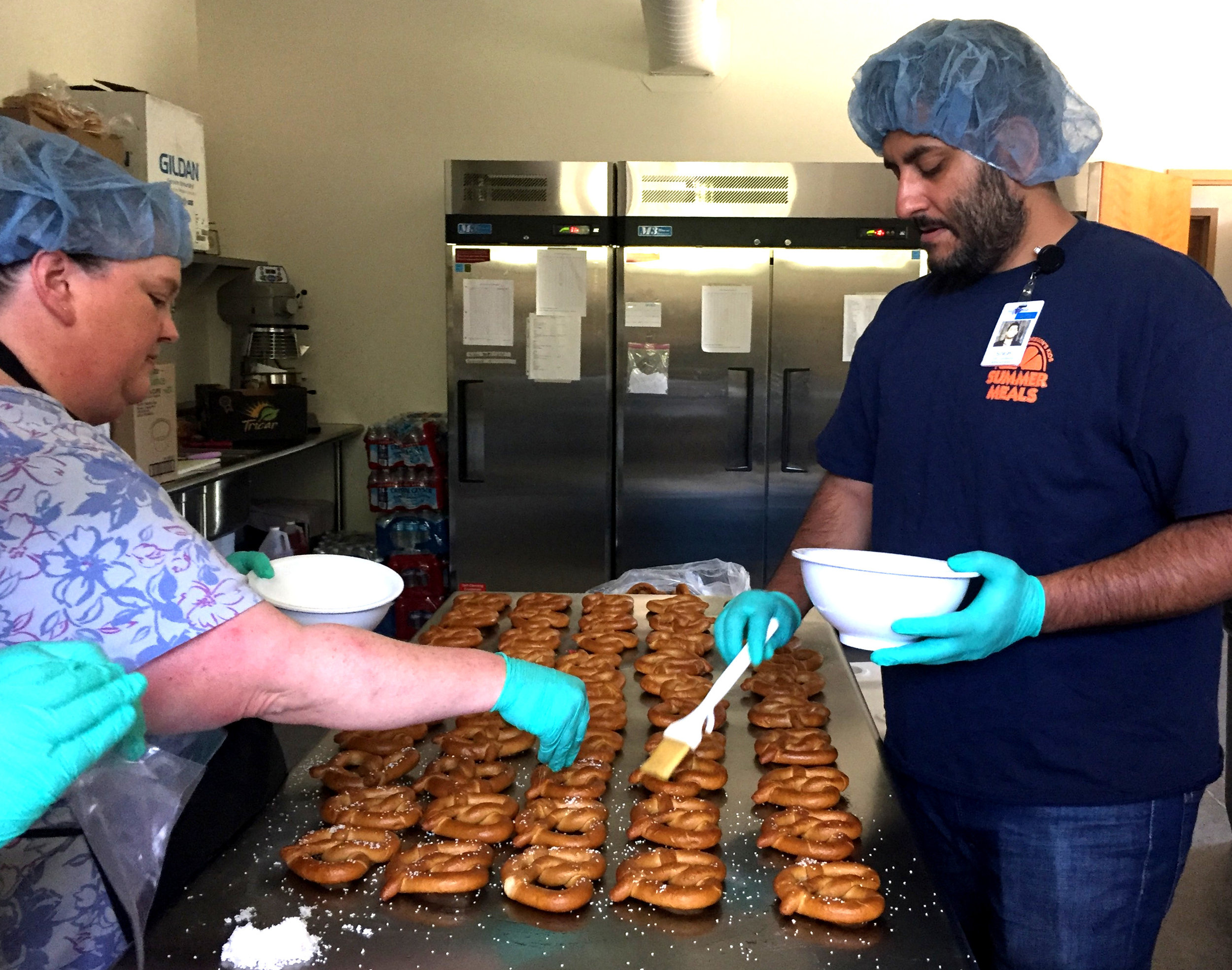 Outback Strong Summer Lunch Program cook Rebecca McMahan, left, and program coordinator Arvinder Singh prepare pretzels for a Wednesday lunch. ( Brooke Kelleher photo |    FoodCorps  )