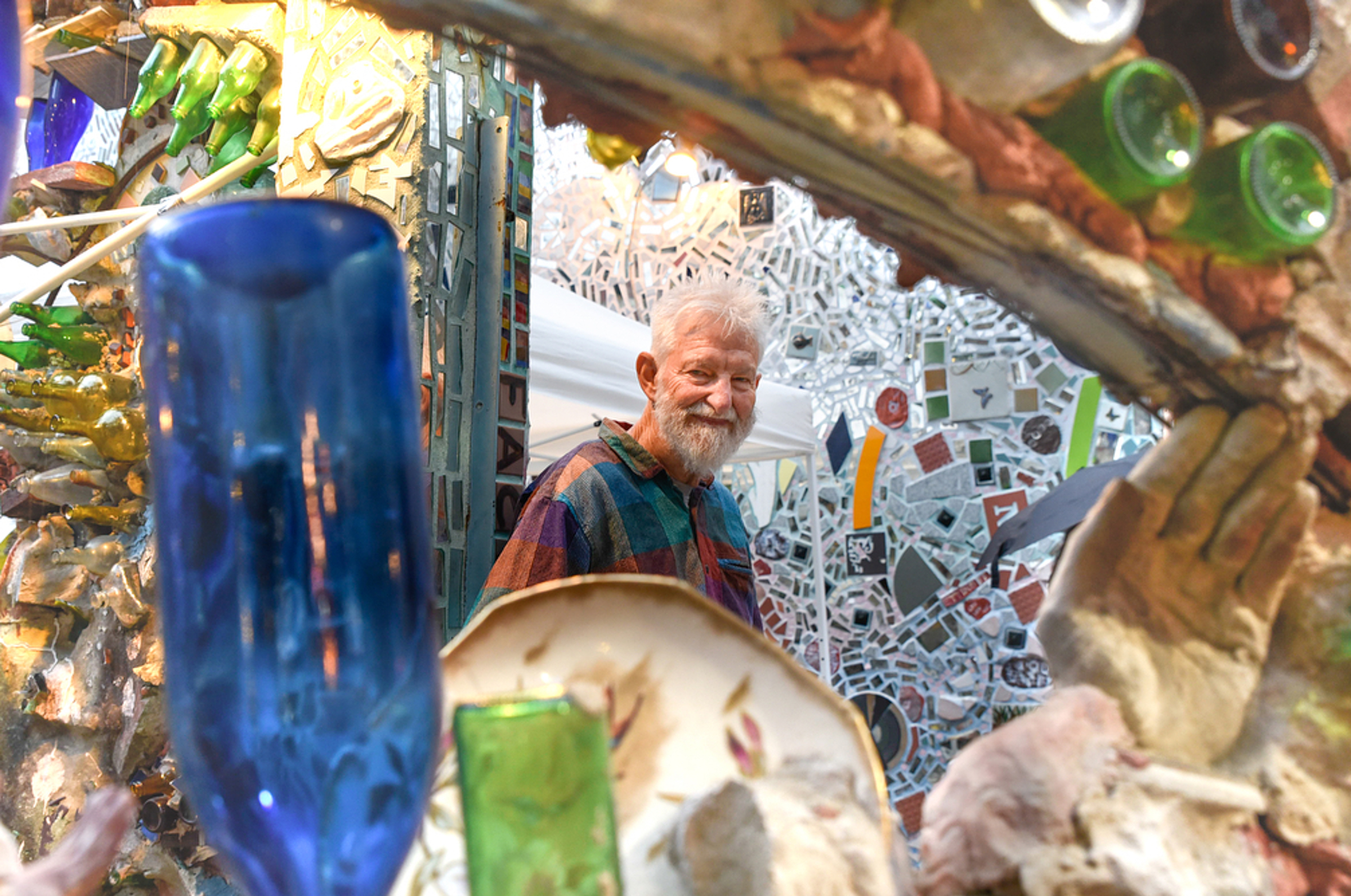 Isiah Zagar is the artist and mastermind behind the Magic Gardens. This South Street institution is a mosaic wonderland filled with folk art, glittery mirrors and found objects that contributed to the revival of South Street. Zagar made an appearance last night at the monthly Twilight in the Gardens event on June 23, 2018. Brianna Spause / This Is Philly