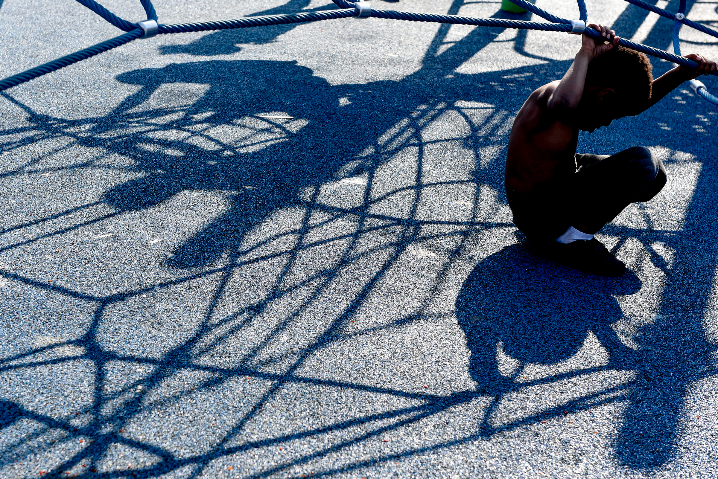 A young boy rests in the shade on a hot day at the Fairhill Square Playground ribbon cutting in North Philadelphia on April 13, 2018. Brianna Spause / Philadelphia Parks & Recreation