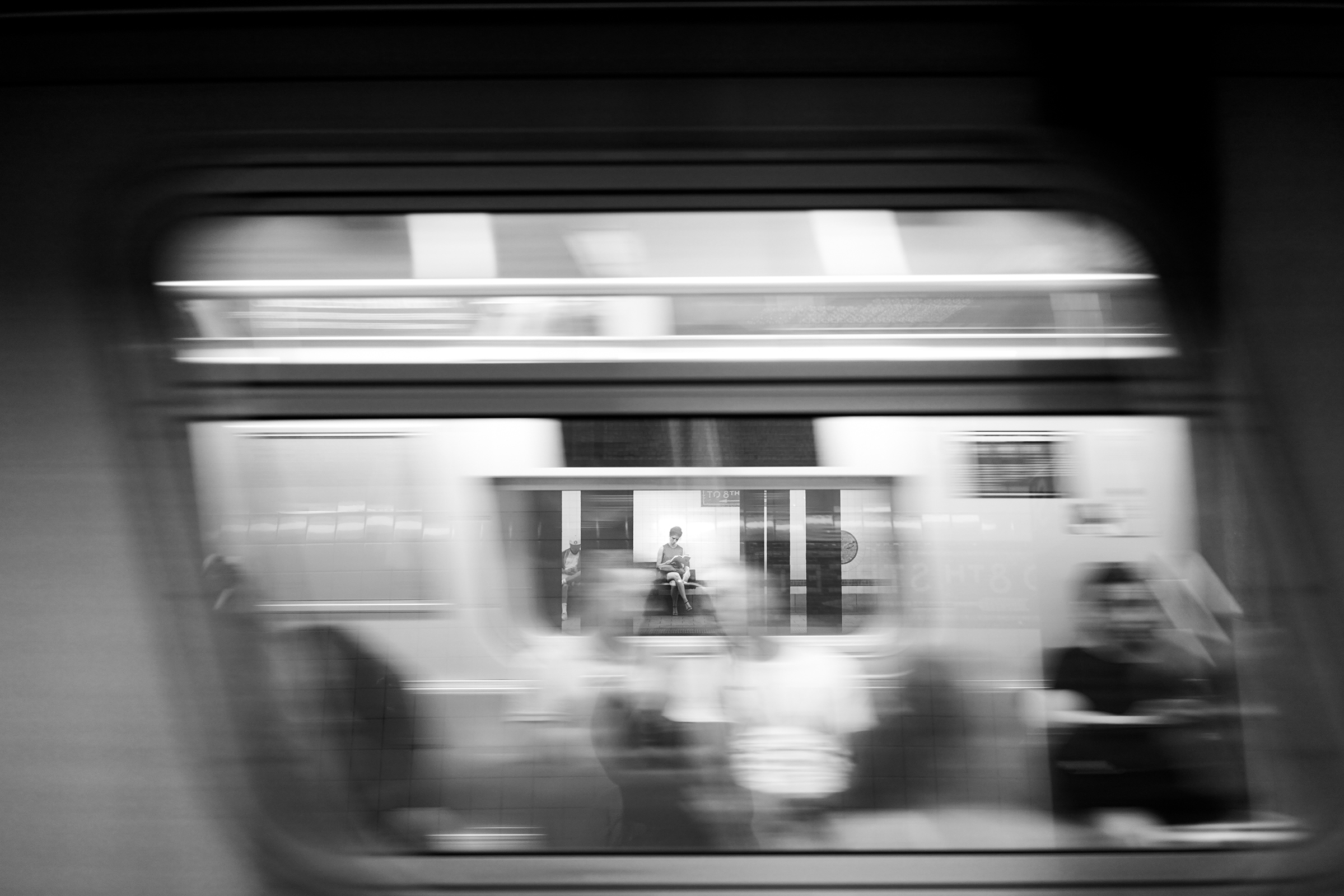A woman reads while waiting for the train at the World Trade Center 3 subway stop on June 29, 2018. / Brianna Spause