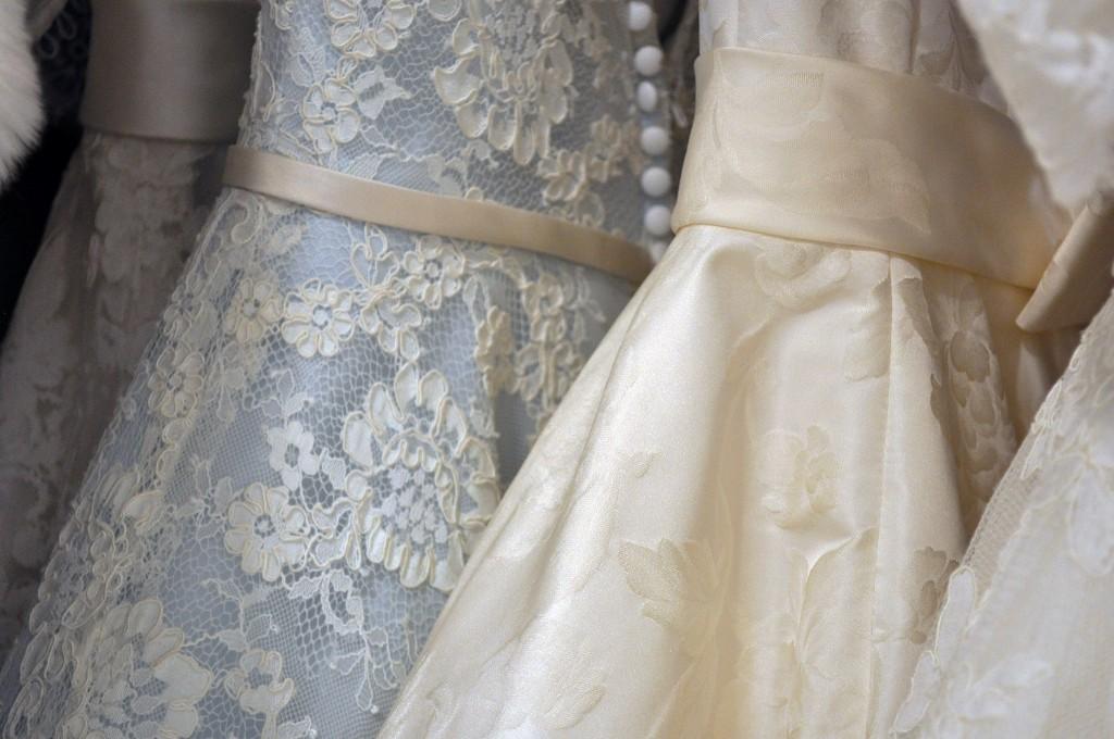 Three wedding dresses hanging on a rack.jpg
