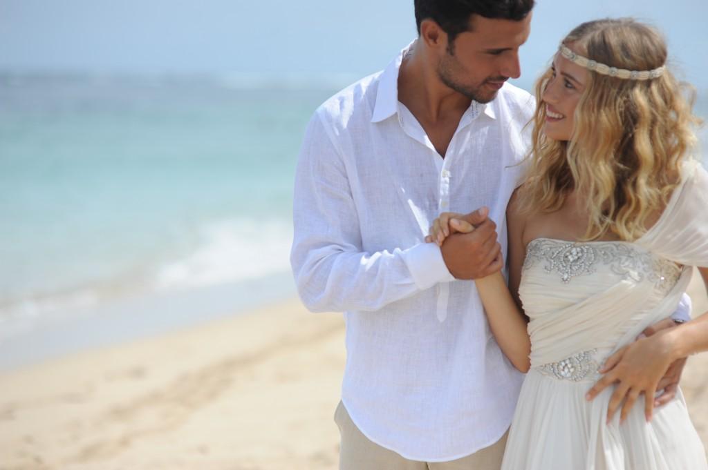 A newly married couple walk the beach.jpg