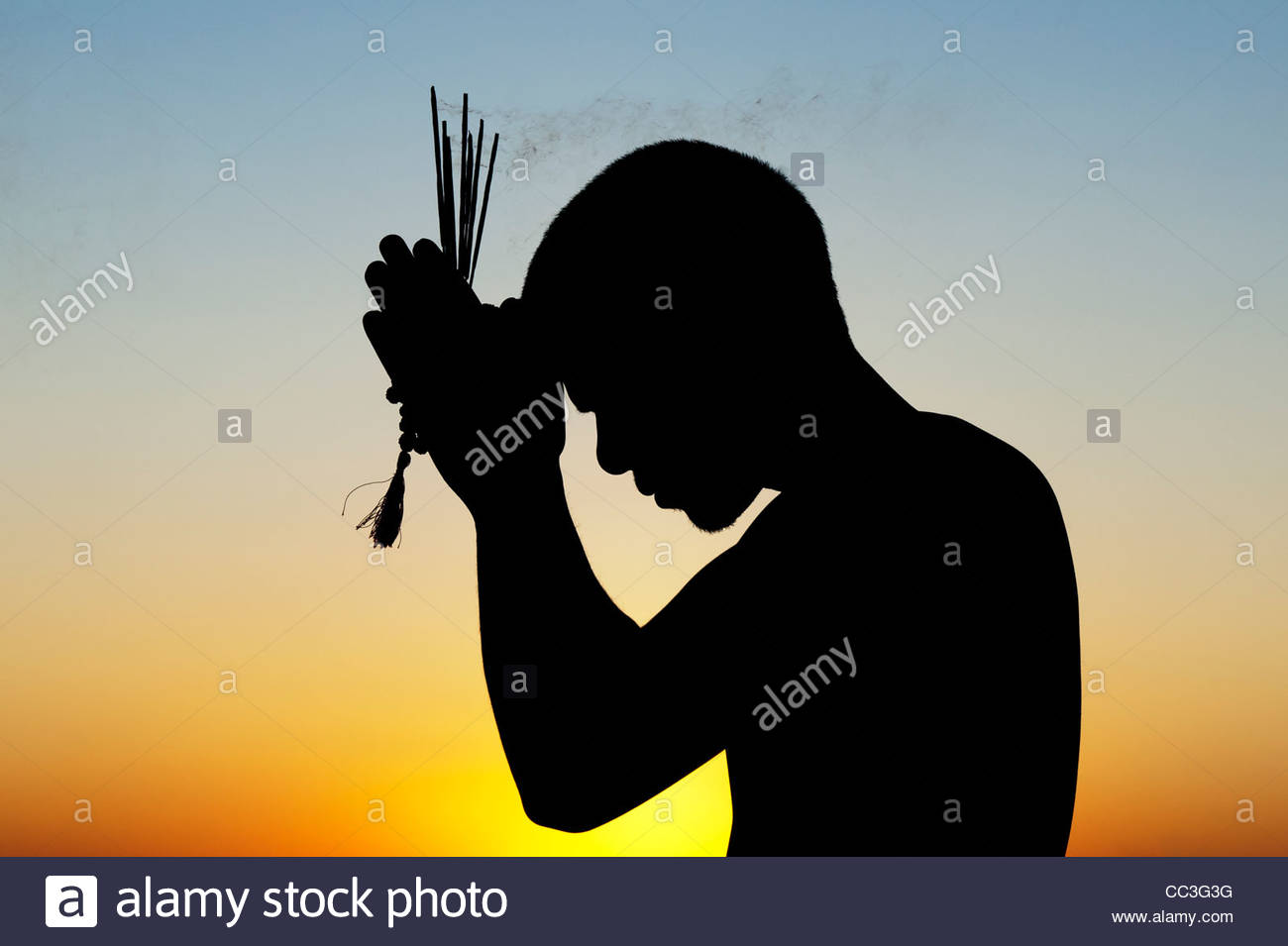 praying-indian-man-with-incense-sticks-at-sunset-silhouette-india-CC3G3G.jpg