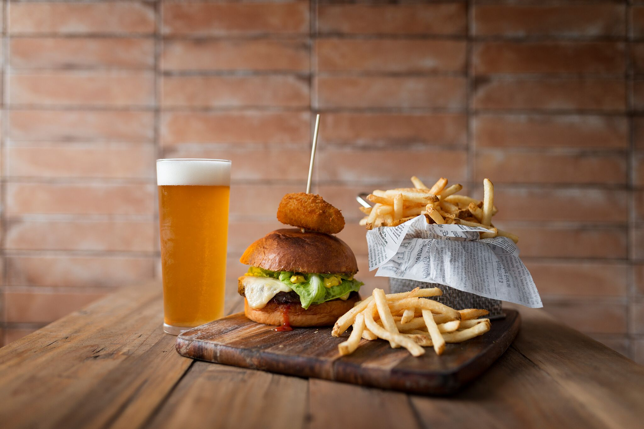Happy hour food - Cheeseburger and fries paired with a glass of lite beer