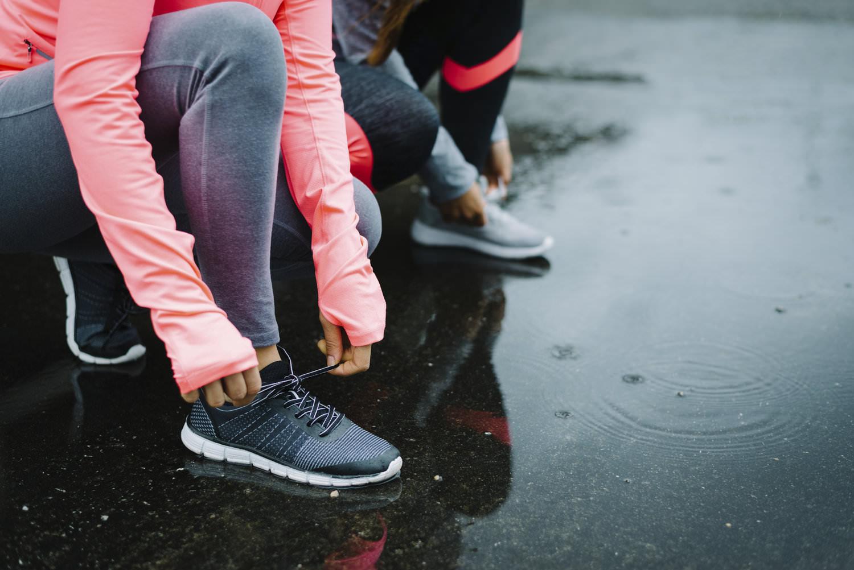 woman runner tying shoelaces on rainy day.jpeg