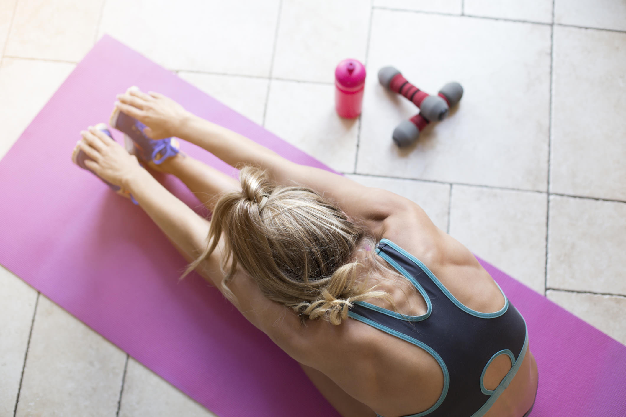woman stretching on pink yoga mat.jpg