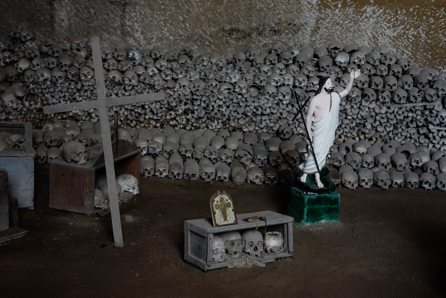 """In 1872 Don Gaetano Barbati, a local priest, and the community members cleaned and rearranged the huge number of skulls and bones and put them in order throughout the various spaces in the cavity. Since then, there has been a very strong devotion for these unidentified remains. Skulls were put in wooden boxes or into special glass because the devotees """"(…) identified in them the souls of the purgatory that needed special care and attention"""". In exchange for this care the skulls are asked to fulfill wishes and to predict the future.  Since its excavation the quarry has converted into a cultural space. Though it is said that mainly people from lower classes were put there, without being named or labelled, all skeletons look similar and are given new meanings through local community members.  Sources:  A. Scotto di Santolo et al. 2013 """"The Fontanelle Cemetery: between legend and reality.""""  Sophia Seymour 2018 """"Naples' Fontanelle cemetery: skulls and silence beneath the busy city streets."""""""
