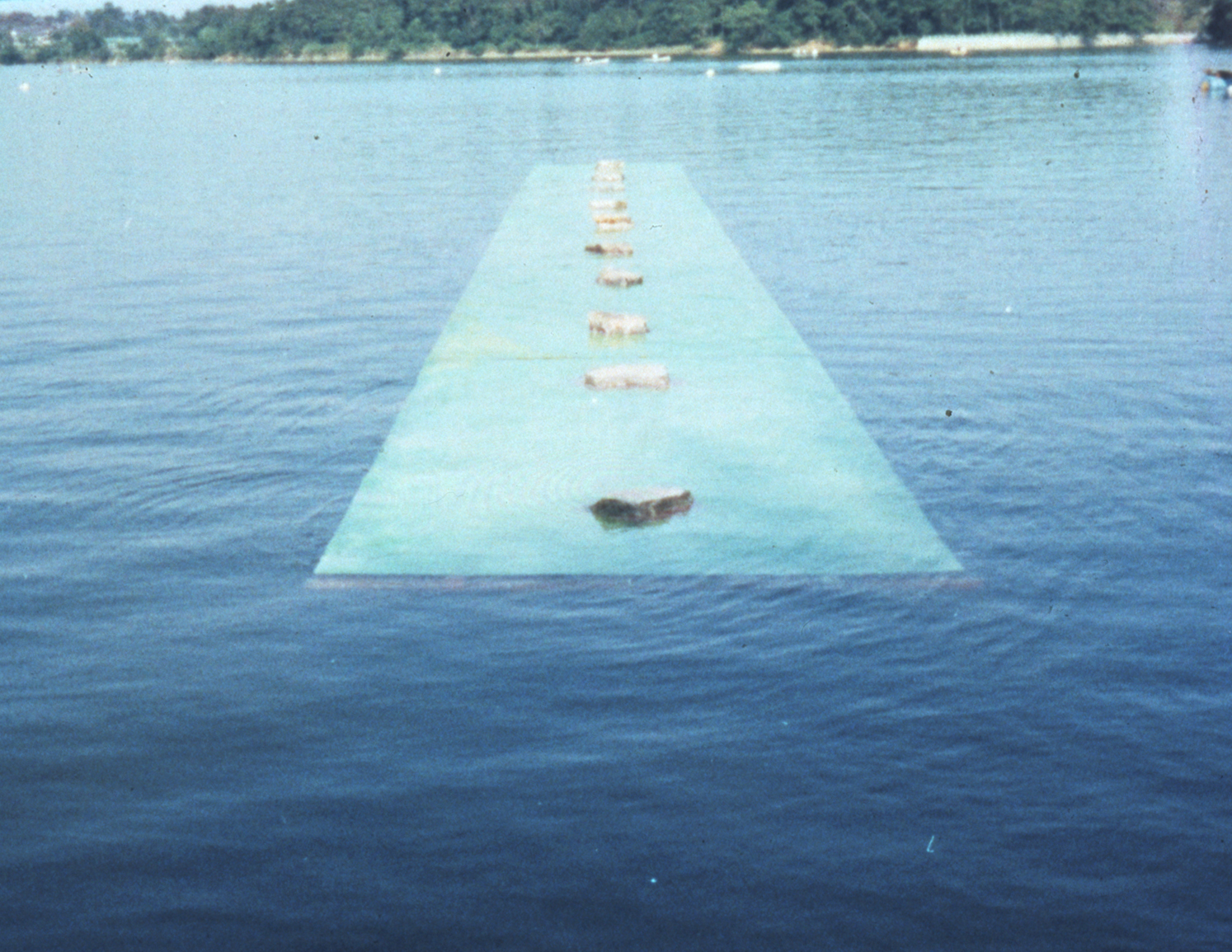 Law of Situation , 1971 状況律 ( Jōkyōritsu ) Stones, plastic board, water 2100 x 240 x 50 centimeters Installation view,  4th Modern Japanese Sculpture Exhibition , Ube City Open-Air Museum, Ube, 1971 Photo: Kishio Suga