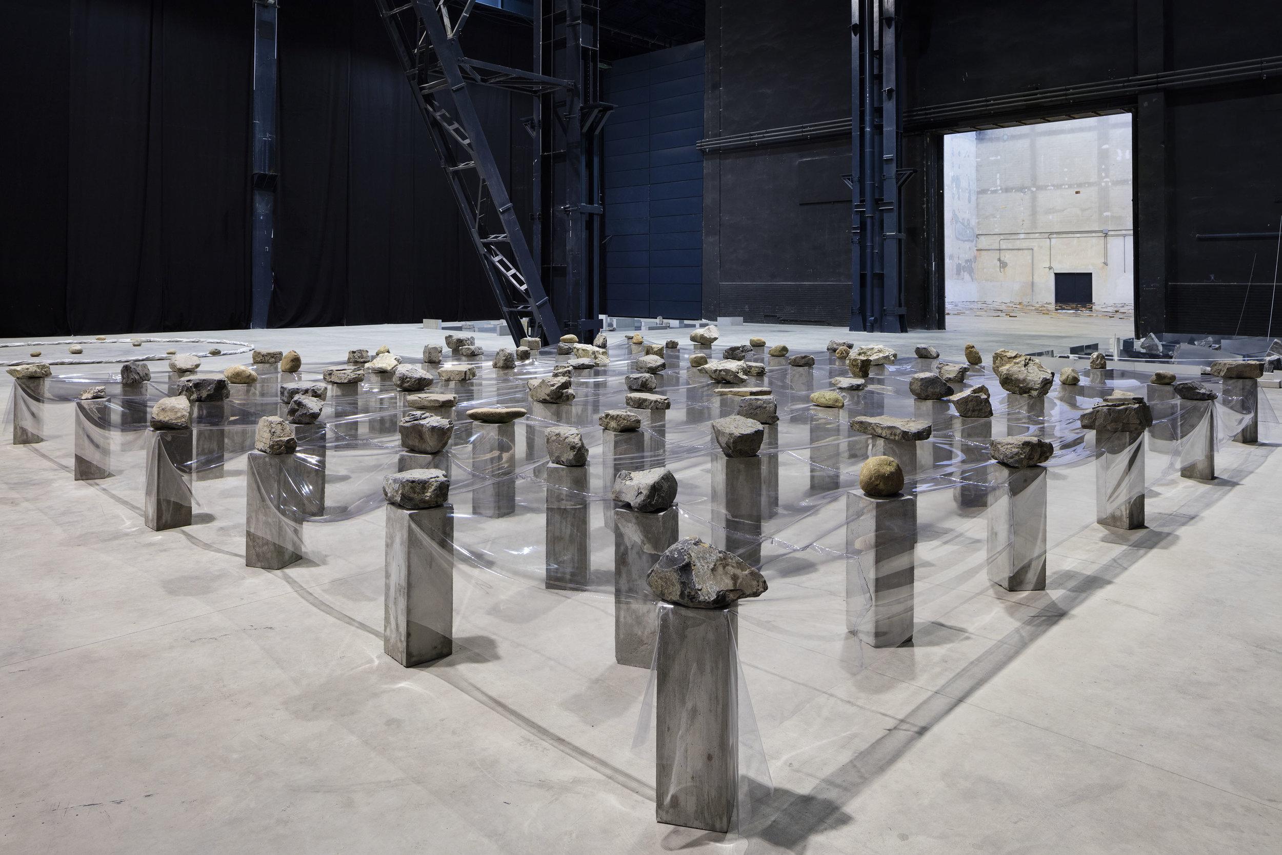 Law of Multitude , 1975/2016 多分律 ( Tabunritsu ) Plastic sheet, stone, concrete 100 x 875 x 850 cm Installation view, Kishio Suga: Situations , Pirelli HangarBicocca, Milan, 2016 Photo: Agostino Osio; Courtesy Pirelli HangarBicocca, Milan