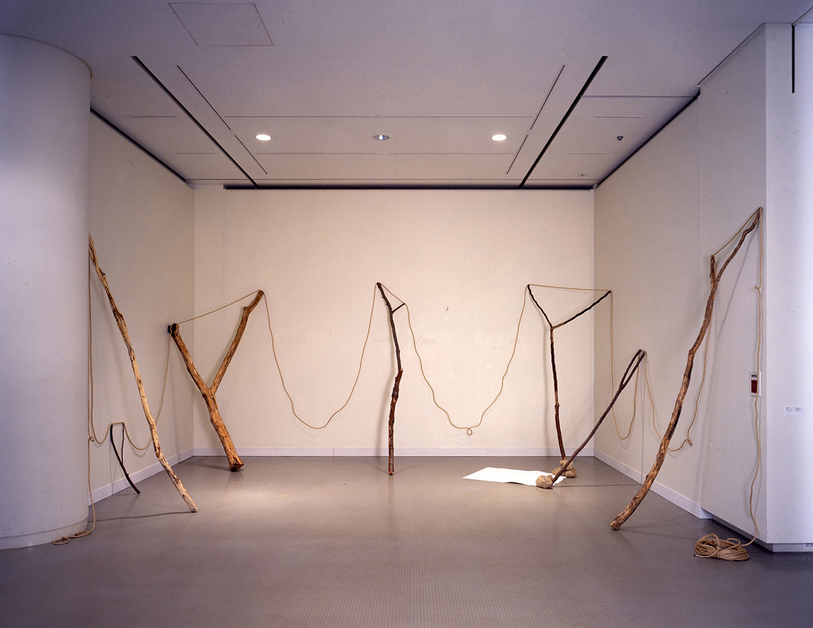 Continuous Existence , 1977/1997 連界 ( Renkai ) Rope, branches, stones, paper Dimensions variable Installation view,  Kishio Suga , Hiroshima City Museum of Modern Art, 1997 Courtesy Hiroshima City Museum of Modern Art
