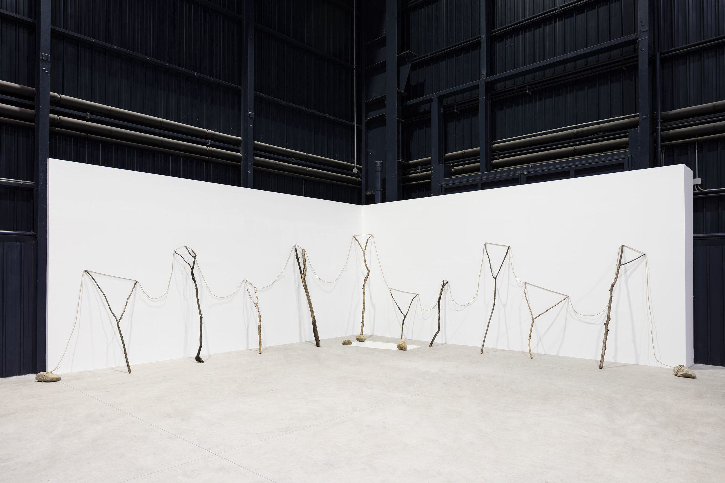 Continuous Existence—HB , 1977/2016 連界—HB ( Renkai—HB ) Rope, branches, stones, painted zinc plate Dimensions variable Installation view,  Kishio Suga: Situations , Pirelli HangarBicocca, Milan, 2016 Photo: Agostino Osio; Courtesy Pirelli HangarBicocca, Milan