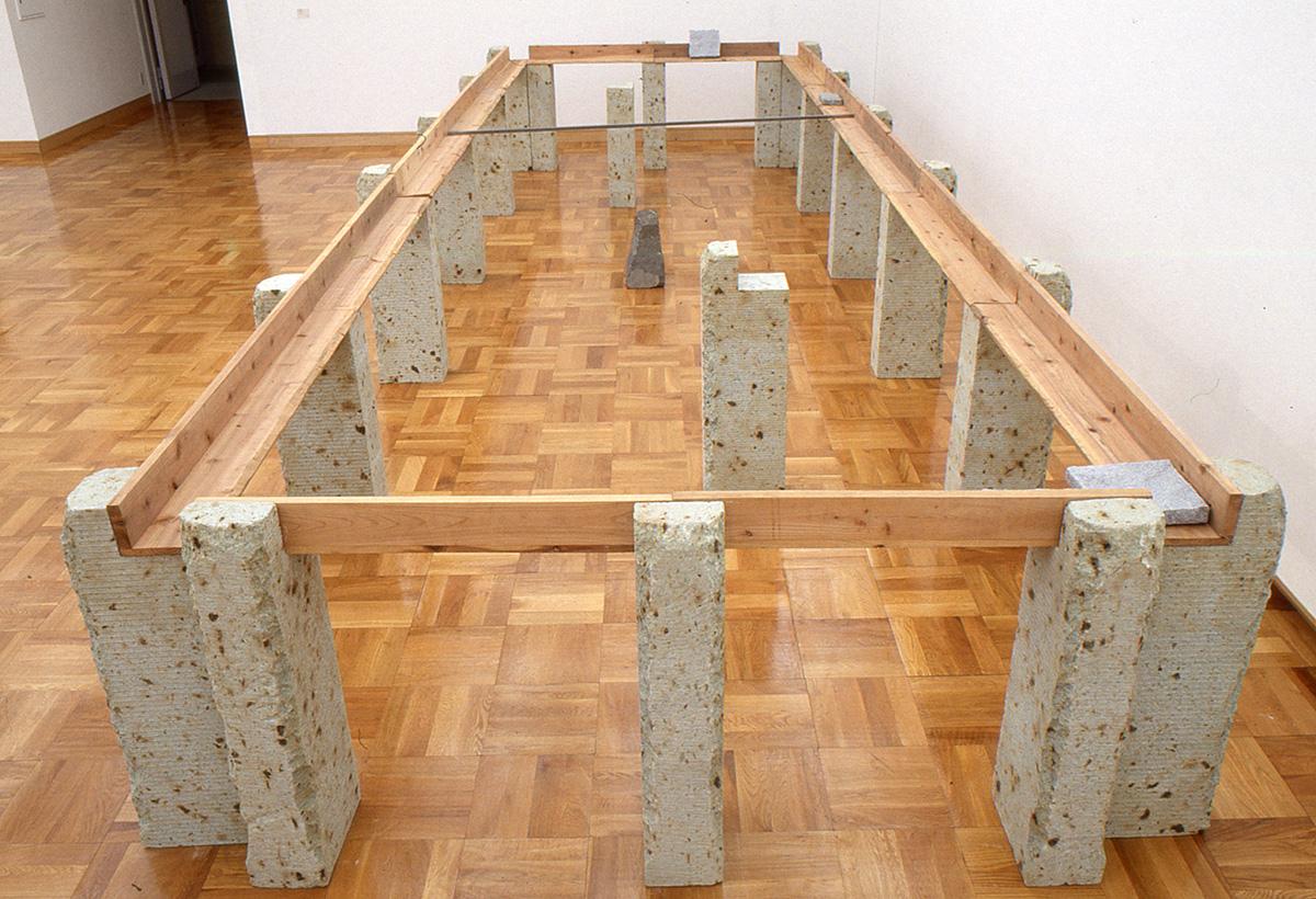 Supported Surrounding , 1987 縁辺仕帯 ( Enpen Shitai ) Wood planks, stone, aluminum 41 3/8 x 103 3/4 x 305 1/2 inches overall Installation view, Kishio Suga ,Chiba City Museum of Art, Chiba, 1998 Courtesy Chiba City Museum of Art