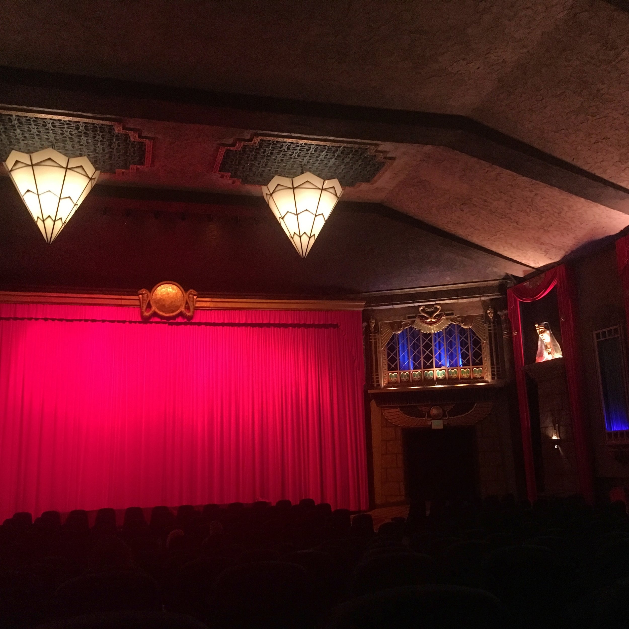 Art Deco movie theater red curtain with chandeliers and seats.