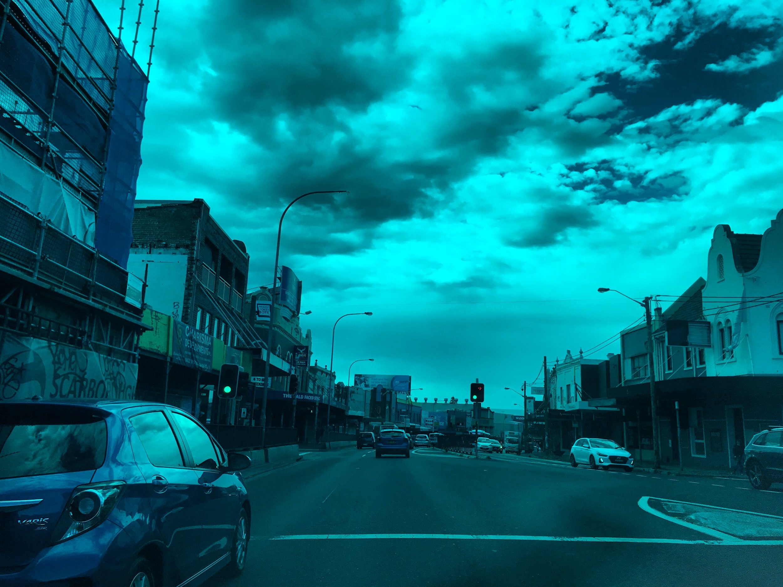 Sydney, Australia street with buildings to left and right and cars in street with teal filter.