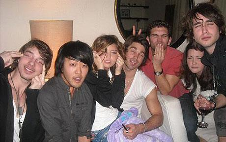 Miley Cyrus and a group of white people mock Asians while sitting with an Asian man.