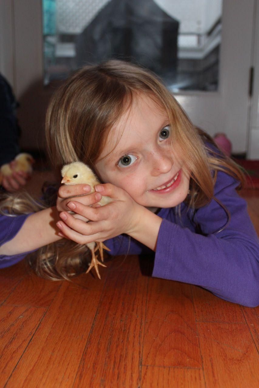 Girl holding chick on floor.jpg