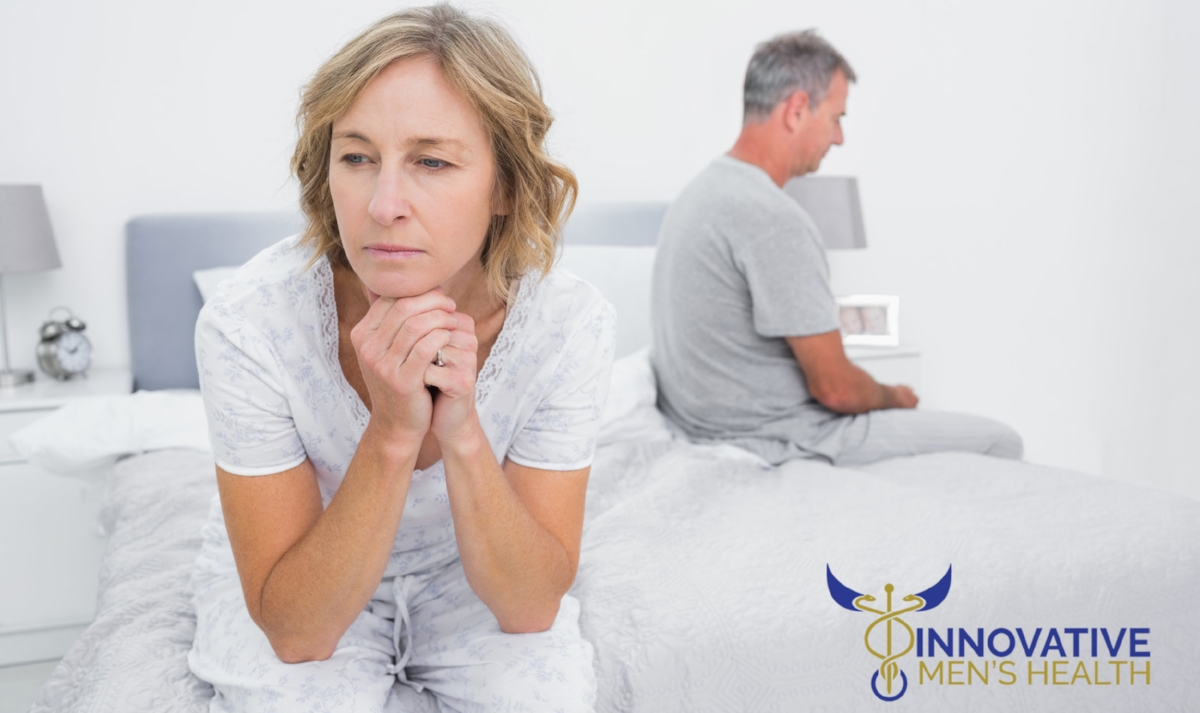 Unhappy couple sitting on different sides of bed having a disput
