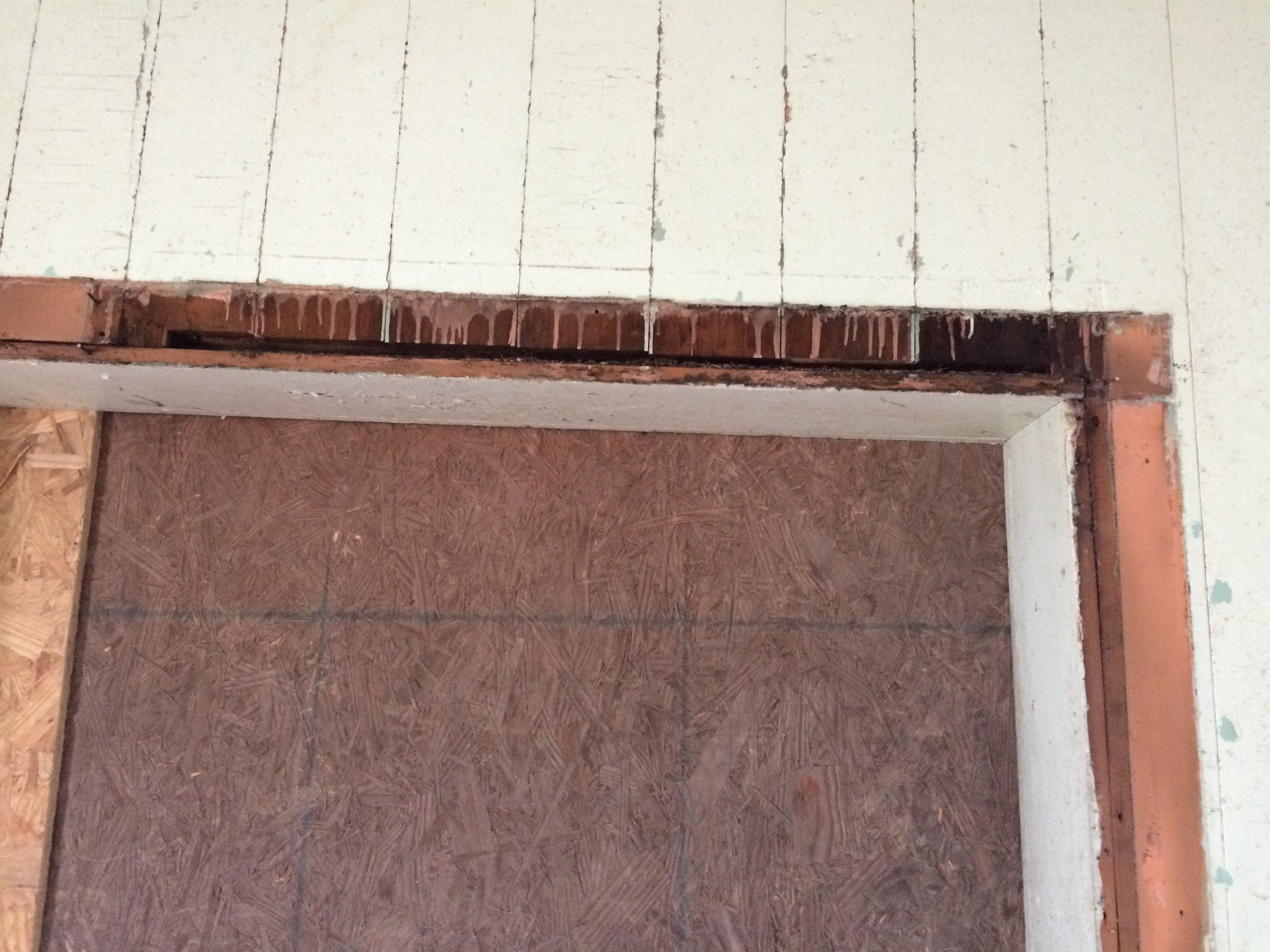 Removal of facing trim on the door opening revealed evidence of an original window.