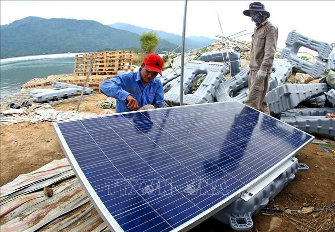 Những tấm pin mặt trời của nhà máy điện mặt trời nổi đang được lắp đặt trên mặt hồ thuỷ điện Đa Mi.