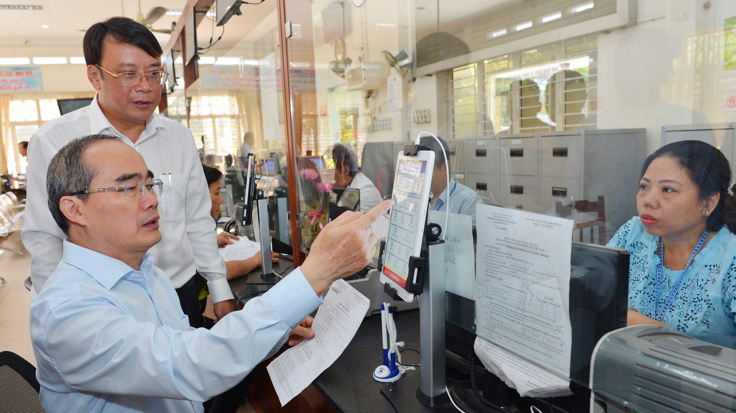 Bí thư Thành uỷ TPHCM Nguyễn Thiện Nhân tìm hiểu dịch vụ hành chính công tại UBND quận Bình Thạnh. Ảnh SGGP