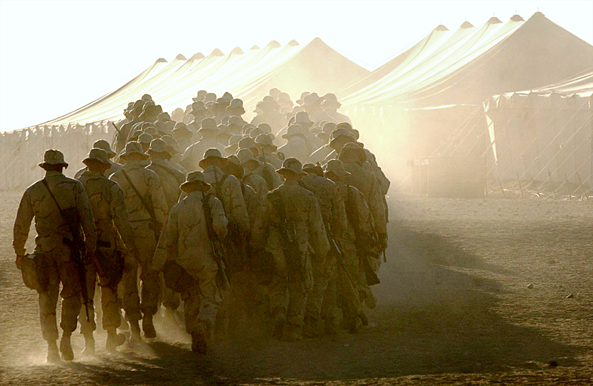 A cloud of dust kicks up as Marines head to the mess hall for breakfast at Camp Coyote in northern Kuwait on March 16, 2003. Over 6000 Marines, seamen and British forces waited in the camp for the U.S.-led strike against Iraq.