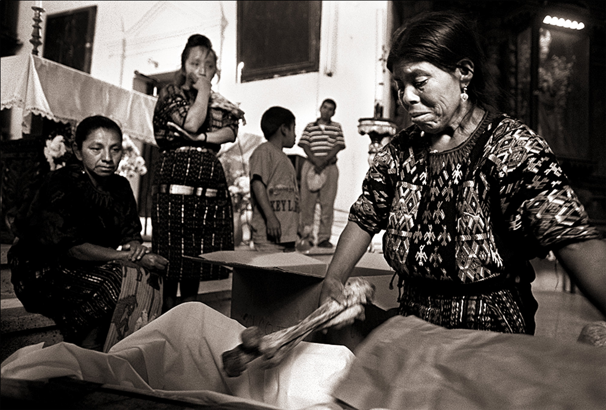 A small coffin becomes the final resting place of Tomas Tian Mejia, murdered in 1982 by the Guatemalan army. His widow, Isabella Mejia, placed the bones of her late husband into the coffin after they were turned over to her at the Iglesia Catolica de Chichicastenango. The bones of 23 people, including her husband's, were discovered and exhumed from a massacre site in the nearby village of Chupol.