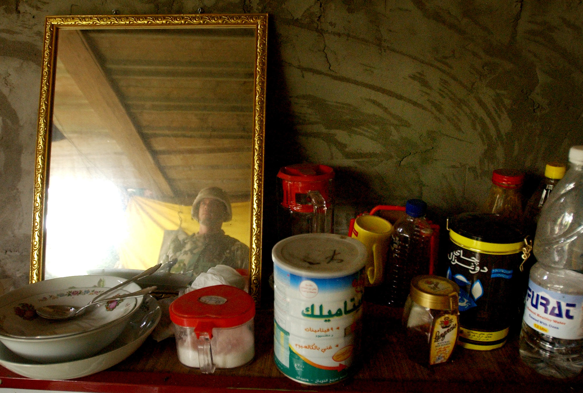 "Food items remain on a counter, including a propped mirror, in the house where deposed Iraqi President Saddam Hussein likely lived when he was caught hiding in a hole on the farm in Al Dawr, near his hometown of Tikrit. ""I am Saddam Hussein. I am the President of Iraq and I am willing to negotiate,"" were Mr. Hussein's words to U.S. Special Forces when he was caught in the hole. ""President Bush sends his regards,"" greeted the soldier, according to the military press officer."